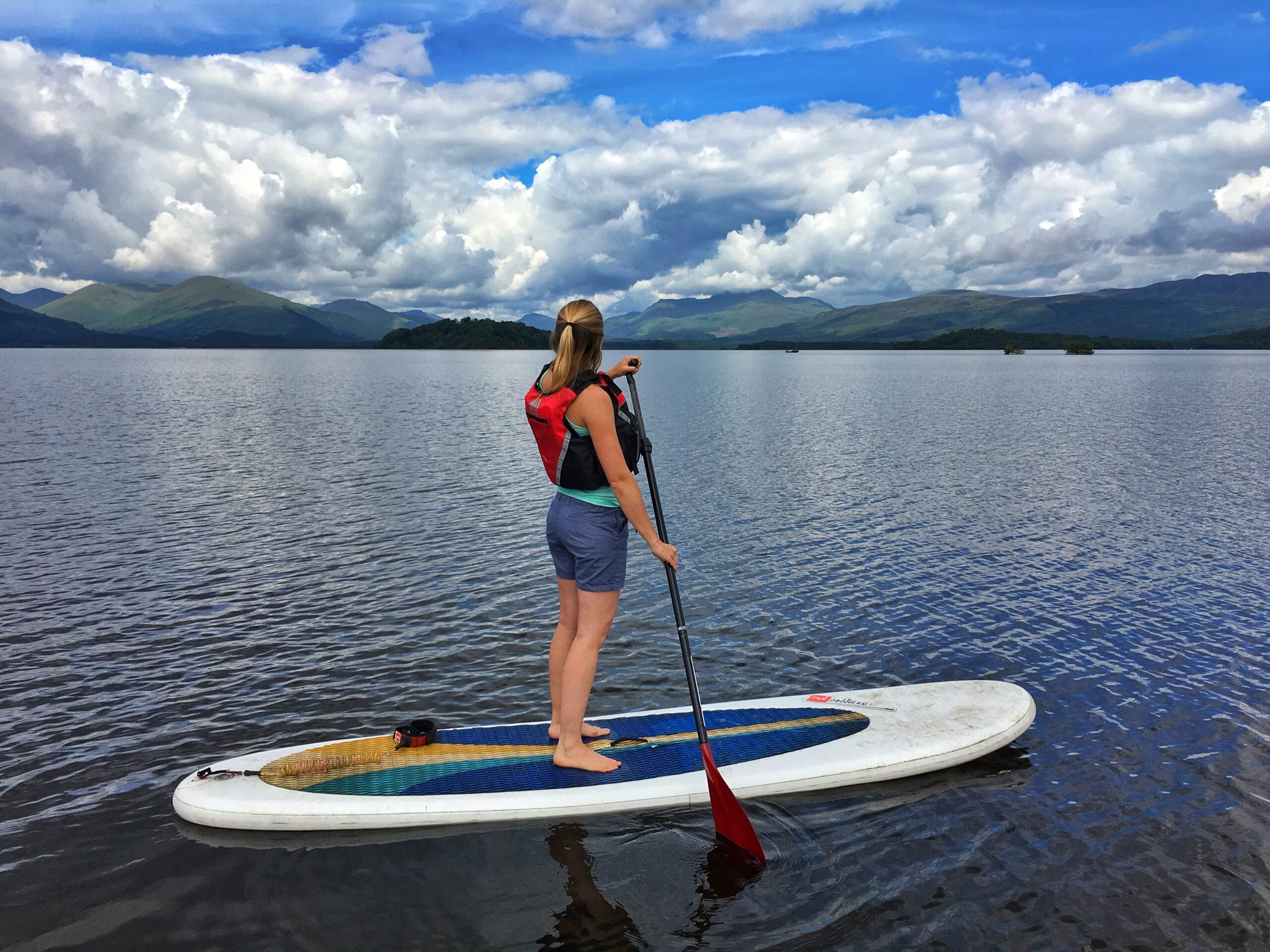 Girl stand-up paddleboarding on Loch Lomond